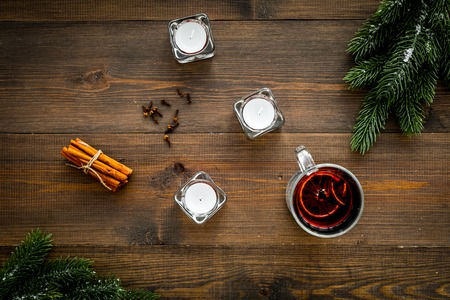 Winter beverage for New Year or Christmas Eve. Mulled wine near fir branches, candles, cinnamon on dark wooden background top view.