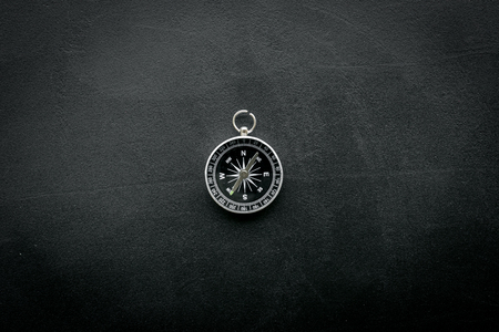 Direction and movement concept with compass on black table background top view mock up 免版税图像