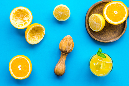 Squeeze fresh oranges with juicer. Orange juice in glass near half cut oranges on blue background top view.