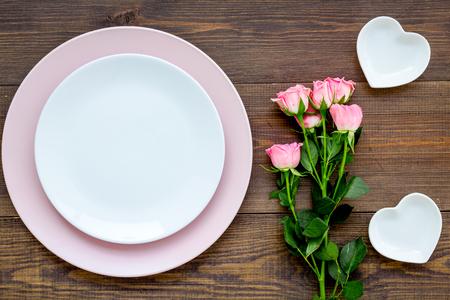Ajuste de la tabla de color simple para la celebración con rosas, platos rosas y platillos en forma de corazón en la vista superior del fondo de la mesa de cocina de madera. Foto de archivo
