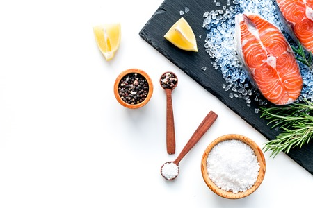 Cooking salmon steak from raw fish on black plate with spices on white restaurant kitchen table background top view copy space.