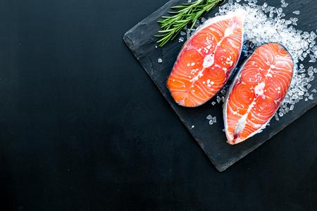 Lachssteak aus rohem Fisch auf schwarzem Teller mit Rosmarin auf dunkelschwarzem Restaurantküchentischhintergrund mit Draufsichtkopienraum kochen. Standard-Bild