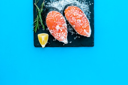 Cooking salmon steak from raw fish on black plate with rosemary on blue restaurant kitchen table background top view copy space.