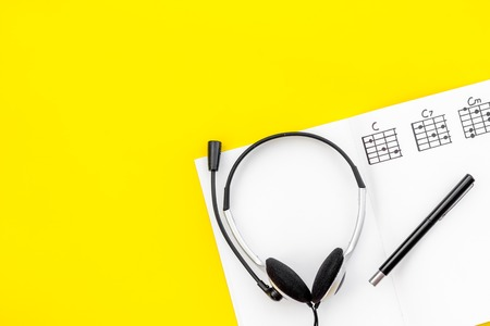 Headphone with paper note in music studio for dj or musician work on yellow background top view space for text Stock Photo