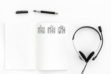 Musician work set with notes and headphones on white table background top view copy space