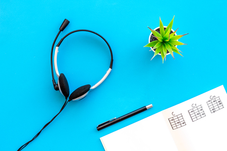 Songwriter or dj work place with notes and headphones on desk blue background top view Stock Photo - 113294772