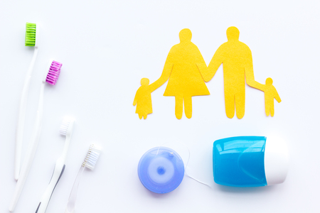 Daily oral hygiene for family. Toothbrush, dental floss and family figures on white table background top view Stock fotó - 113295587