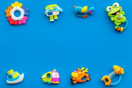 Handmade toys for newborn baby. Rattle. Blue background top view mockup.