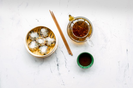 Dim sums with sticks and herbal tea in Chinese restaurant on marble table background top view