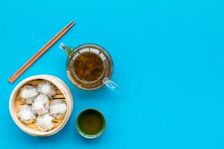 Dim sums with sticks and herbal tea in Chinese restaurant on blue table background top view mockup Stock Photo - 113295594