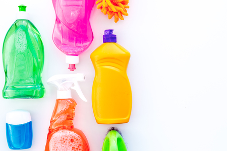 Housecleaning with detergents, soap, cleaners and brush in plastic bottles on white desk background top view mockup