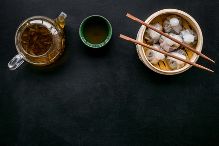 Chinese food set with dim sum, sticks and tea on black desk background top view copy space
