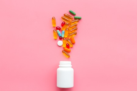 Close up of an open bottle of medicine and its lid. Several pills are lying on pink desk. Pharmacology and medical supplies. Top view mock-up. Banco de Imagens