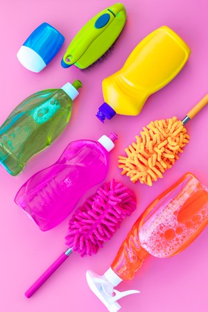 Housekeeping tool. Detergents, soap, cleaners and brush for house cleaner work on pink background top view space for text. Stockfoto