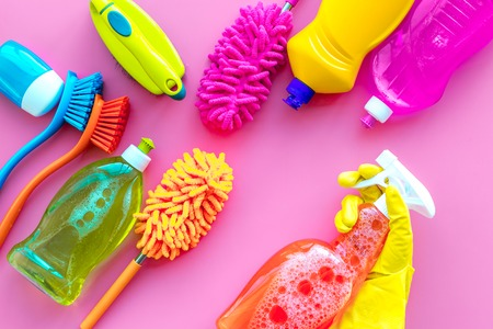 House cleaner tools set with detergents, soap, cleaners and brush on pink background top view mock up.