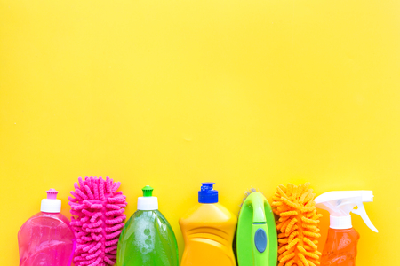 House cleaner tools set with detergents, soap, cleaners and brush on yellow background top view mock up.