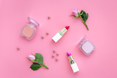Rose tone cosmetics. Lipstick, bulk, eyeshadow among rose flowers on pink background top view.