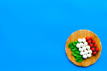 Italian flag made of mozzarella cheese, cherry tomatoes, green basil on wooden cutting board on blue background top view. Stock Photo