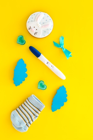 Pregnancy test, socks and hearts on yellow background top view