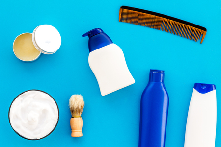 Male care set for barbershop with shampoo bottle and comb on light blue desk background top view mock-up 스톡 콘텐츠