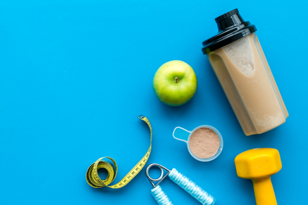 Nutrition for workout with protein cocktail and bars on blue table background top view mockup