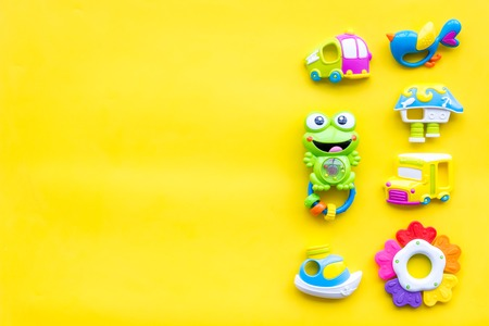 Toys for newborn baby set with plastic rattle on yellow background flat lay space for text. Foto de archivo - 113373749