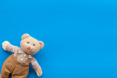 Toys for newborn baby set with teddy bear on blue desk background flat lay space for text Stockfoto