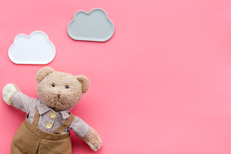 Baby care with craft toys for newborn. Teddy bear. Pink desk background top view copy space Stockfoto