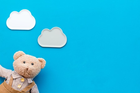 Handmade toys for newborn baby. Teddy bear. Blue background top view mockup.