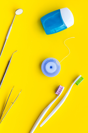Daily oral hygiene for family. Toothbrush, dental floss and dentist instruments on yellow table background top view