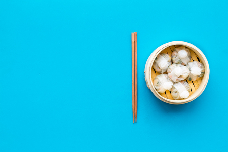 Dinner in Chinese restaurant with dim sum, sticks on blue table background top view space for text Stok Fotoğraf
