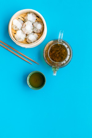 Chinese steamed dumplings Dim Sum in bamboo steamer with tea on blue table background top view mock up