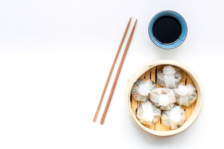 Dim sums with sticks and black tea in Chinese restaurant on white table background top view mockup