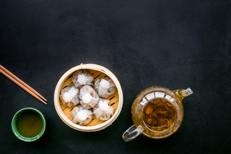 Dim sums with sticks and herbal tea in Chinese restaurant on black table background top view mockup