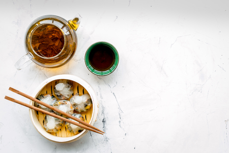 Dim sums with sticks and herbal tea in Chinese restaurant on marble table background top view mockup Reklamní fotografie