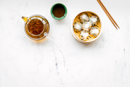 Dim sums with sticks and herbal tea in Chinese restaurant on marble table background top view mockup Stock Photo