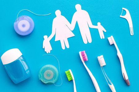 Tooth care with toothbrush, dental floss and family figures. Set of cleaning products for teeth on blue table background top view Banco de Imagens