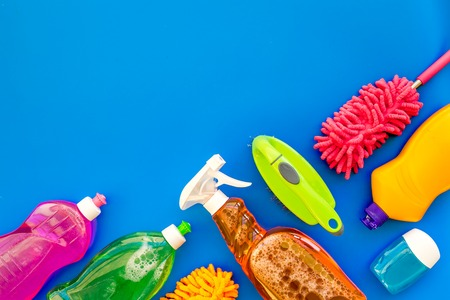 Housecleaning with detergents, soap, cleaners and brush in plastic bottles on blue desk background top view mockup
