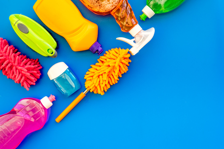 Housekeeping set. Detergents, soap, cleaners and brush for housecleaning on blue background top view mock-up.