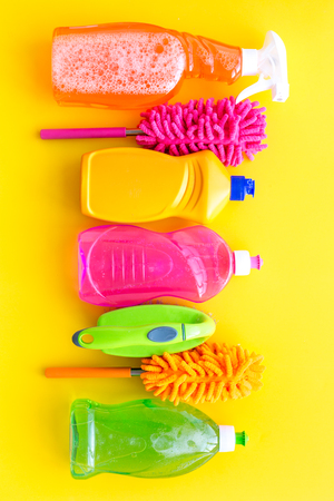Housecleaner tools set with detergents, soap, cleaners and brush on yellow background top view mock up.
