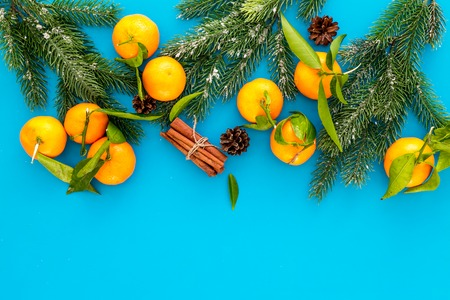 Winter fruits for New Year and Christmas. Tangerines on blue table background top view mock-up