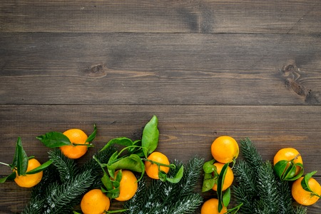 Pile of tangerines, fir tree for New Year and Christmas celebration on wooden table background top view mock up