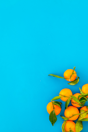 New Year and Christmas Eve with mandarins. Citrus winter fruits on blue table background top view space for text