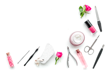 Manicure equipment with nail polish and rose petals on white background top view space for text