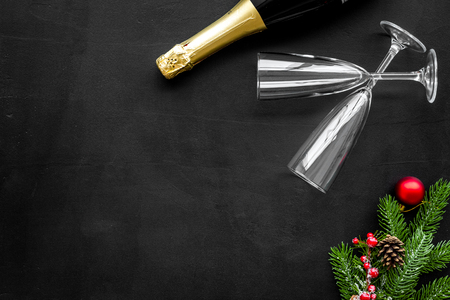 New Year 2019 celebration with spruce branch, champagne and glasses on black table background top view mock up