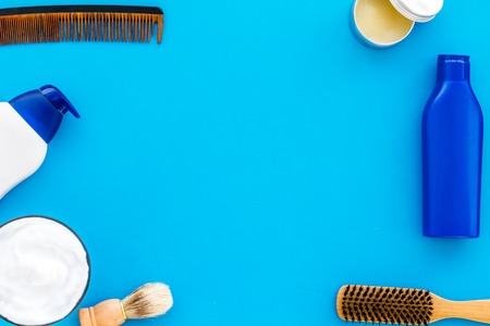 Barber workspace with equipment. Shampoo bottle and comb on light blue table background top view space for text
