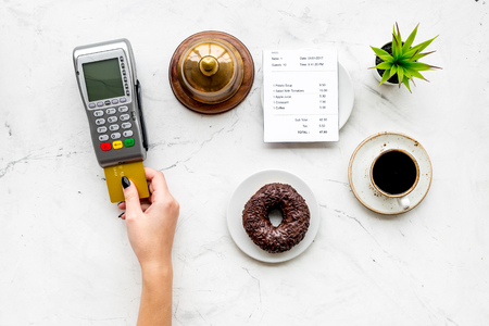 Pay the bill by payment terminal. Womans hand insert bank card in payment terminal near bill, service bell, coffee on white stone background top view.