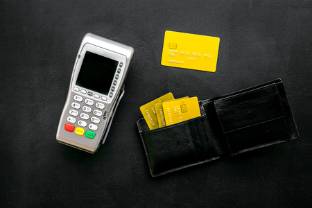 Pay by bank card, pay by credit card. Payment terminal near card and wallet with bank and credit cards on black background top view.