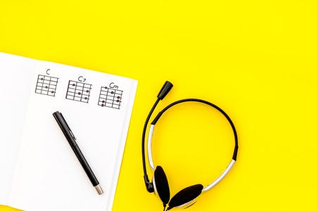 Musician work set with notes and headphones on yellow table background top view copy space