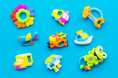 Toys for newborn baby set with plastic rattle on blue background flat lay spattern.